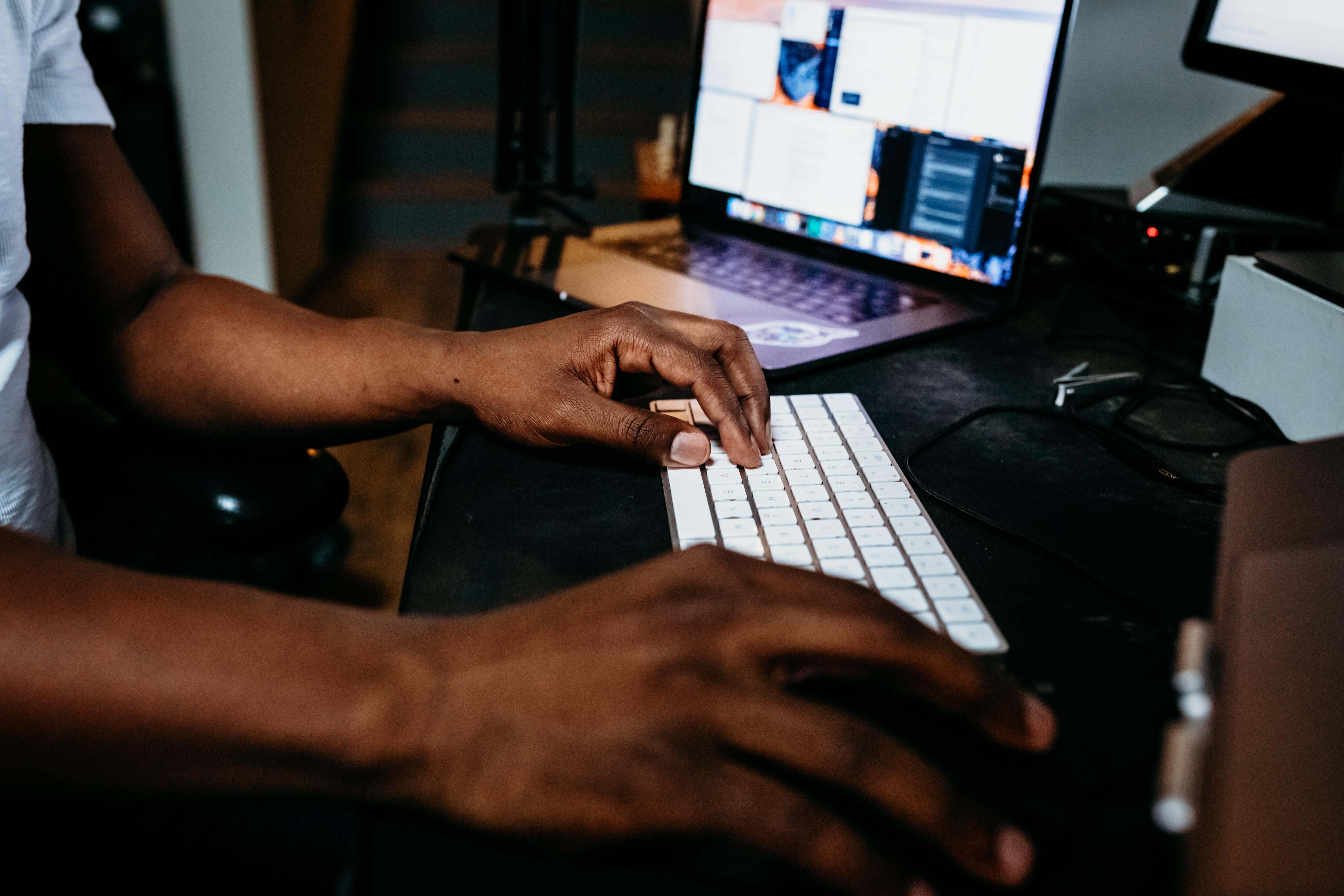 A man sits at a laptop.